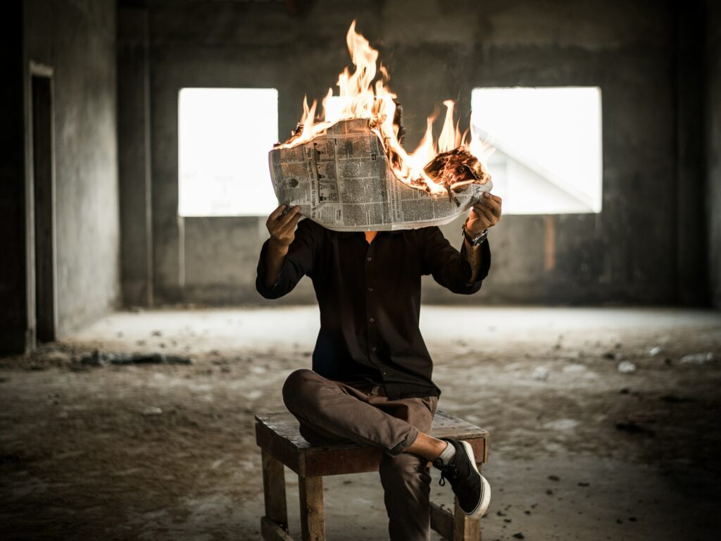 Man holding a newspaper in flames