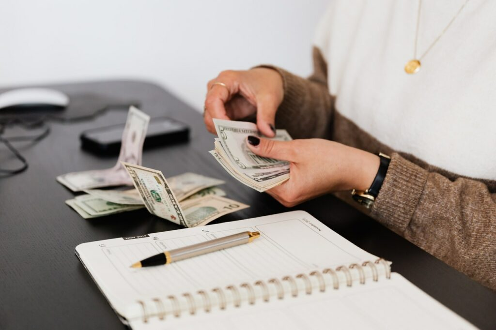 Woman counting her money and making notes