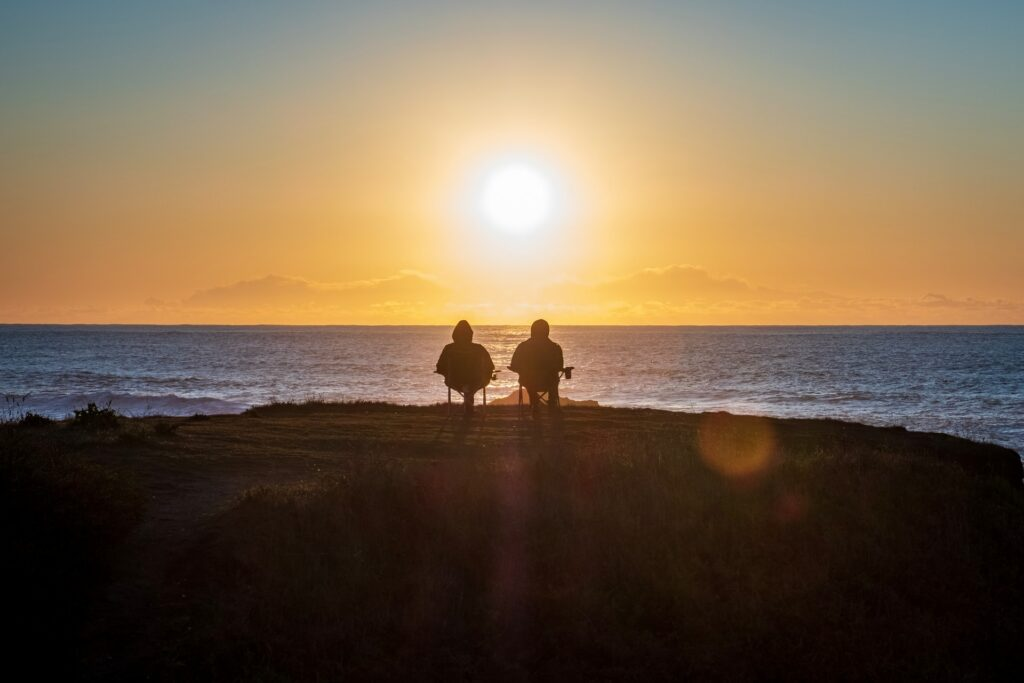 Two people sitting on chairs overlooking a sunset beach