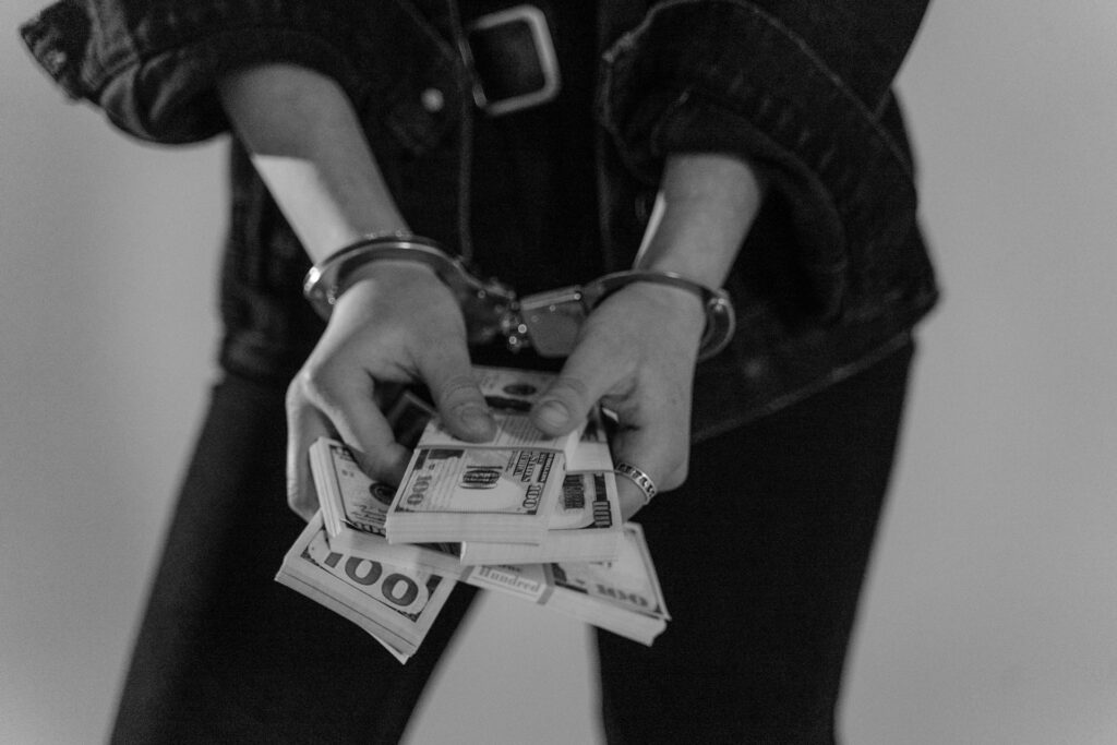 Photo of a person holding cash and wearing handcuffs