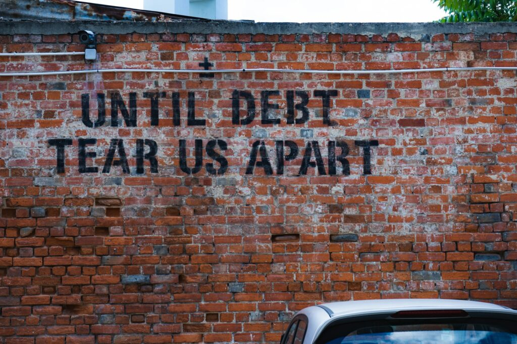 "Brick Wall with Grunge Text ""Until Debt Tear Us Apart"""