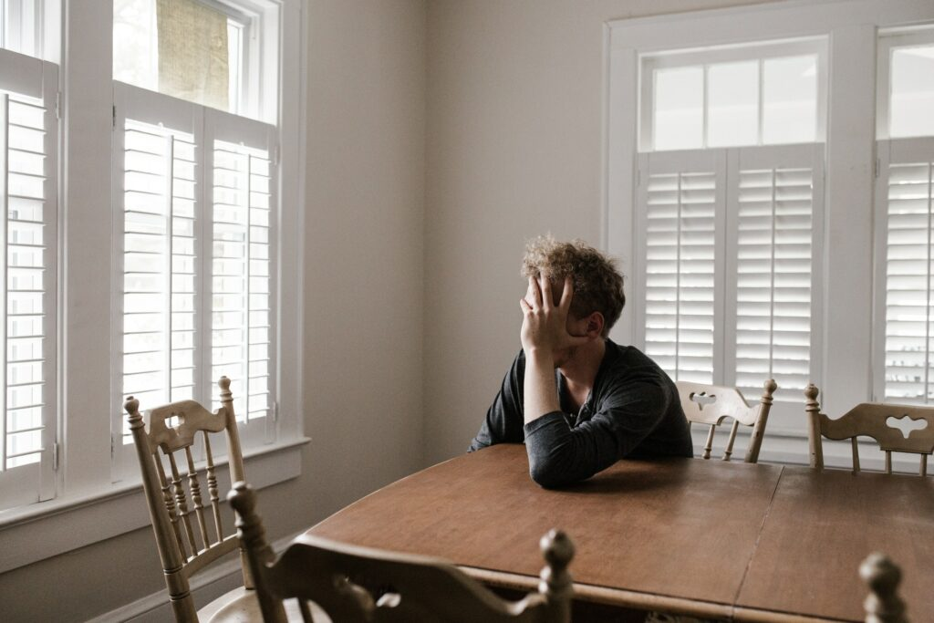 Photo of man sitting at an empty dining table, face covered by hand as he looks toward a bright window