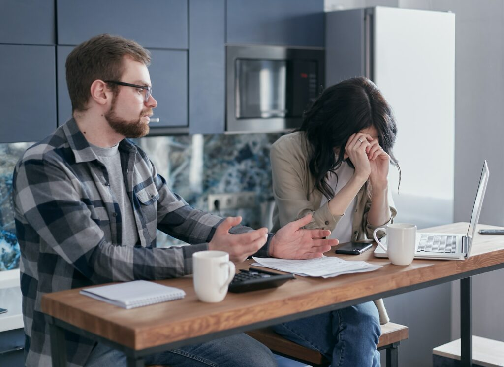 Woman and man going over bills looking frustrated