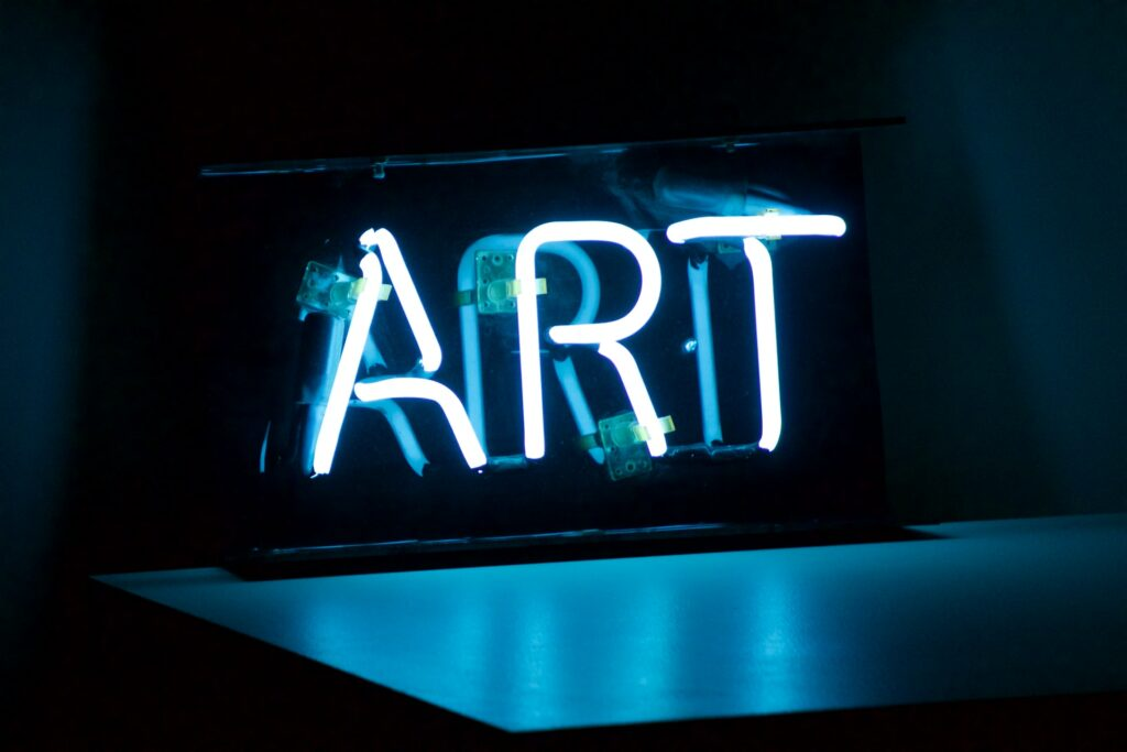 """Blue neon sign that says """"ART"""""""